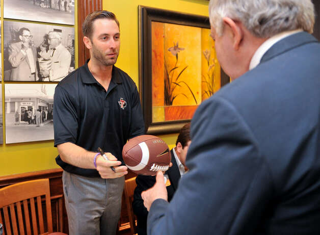 Tech coach Kliff Kingsbury returns an autographed football to Bill Gordon at Monday's luncheon. Photo: Robin Jerstad / For The Express-News