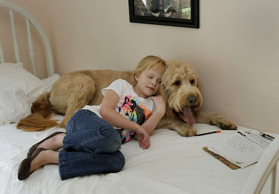 Jenna Partington, who suffers from cystinosis, spends some quiet time with Tucker, the family dog. Photo: Brant Ward, The Chronicle