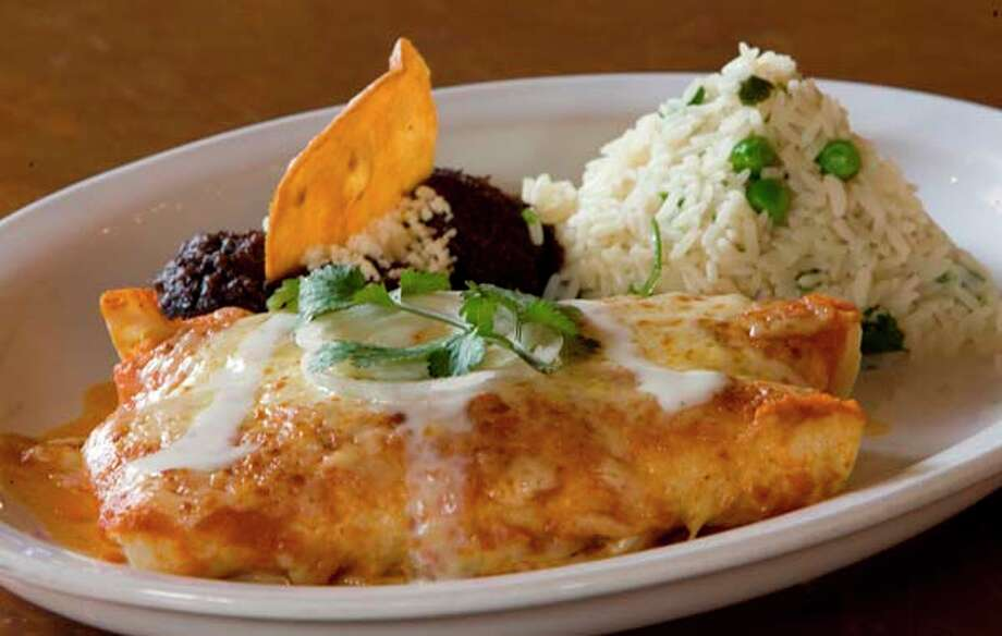 Enchiladas suizas, served with refried beans and rice is a featured dish at Hugo's. Photo: Steve Campbell, Houston Chronicle / Houston Chronicle