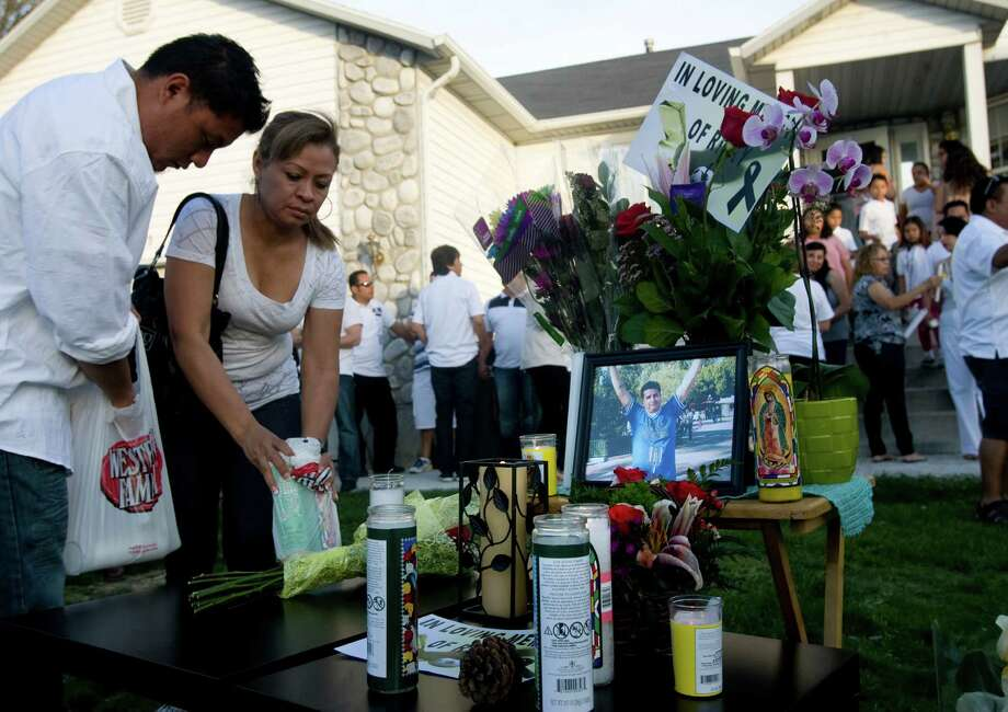 Alex Flores, left, and Silvia Castro place candles at a vigil for Ricardo Portillo, who passed away after injuries he sustained after an assault by a soccer player at a soccer game he was refereeing on April 27, in Salt Lake City on Sunday, May 5, 2013. (AP Photo/The Salt Lake Tribune, Kim Raff) Photo: Kim Raff