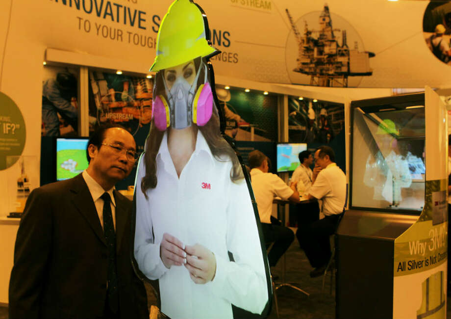 Shouzhong Ma looks over a life size hologram woman on display at the 3M booth at OTC 2013 at Reliant Park Monday, May 6, 2013, in Houston. ( James Nielsen / Houston Chronicle )