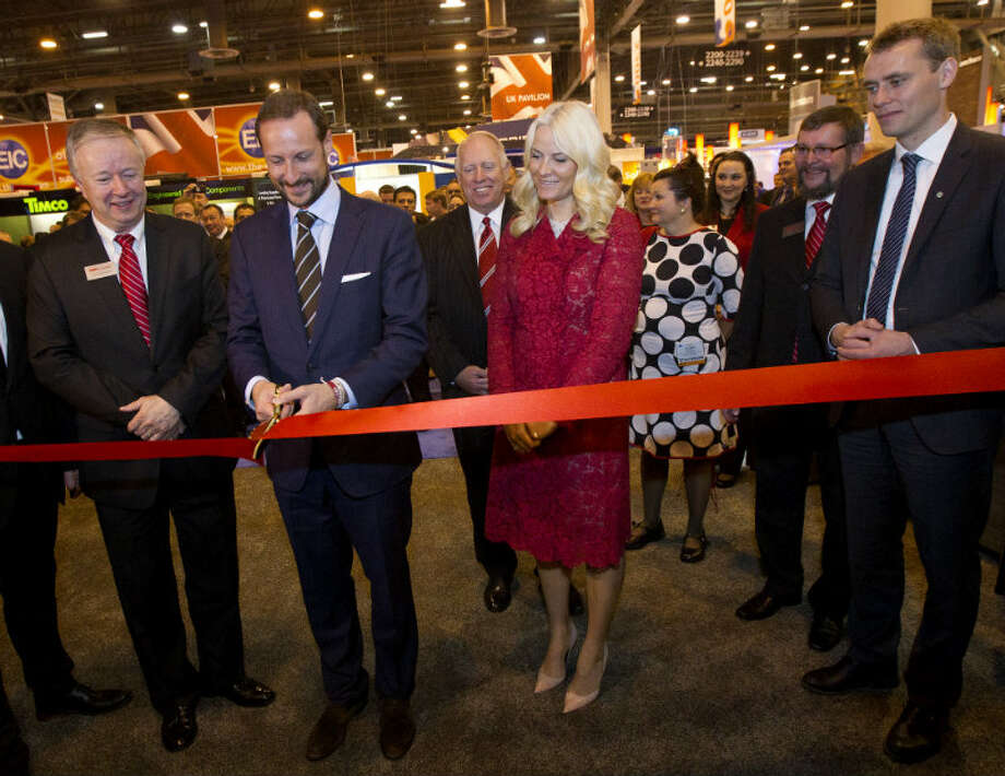 FMC Technologies Tore Halvorsen, left, stands with ...Norway's Crown Prince Haakon, center, Crown Princess Mette-Marit, and petroleum minister Ola Borten Moe, right, as he cuts the ribbon for a new FMC design during the Offshore Technology Conference at Reliant Center Monday, May 6, 2013, in Houston. (Cody Duty / Houston Chronicle)