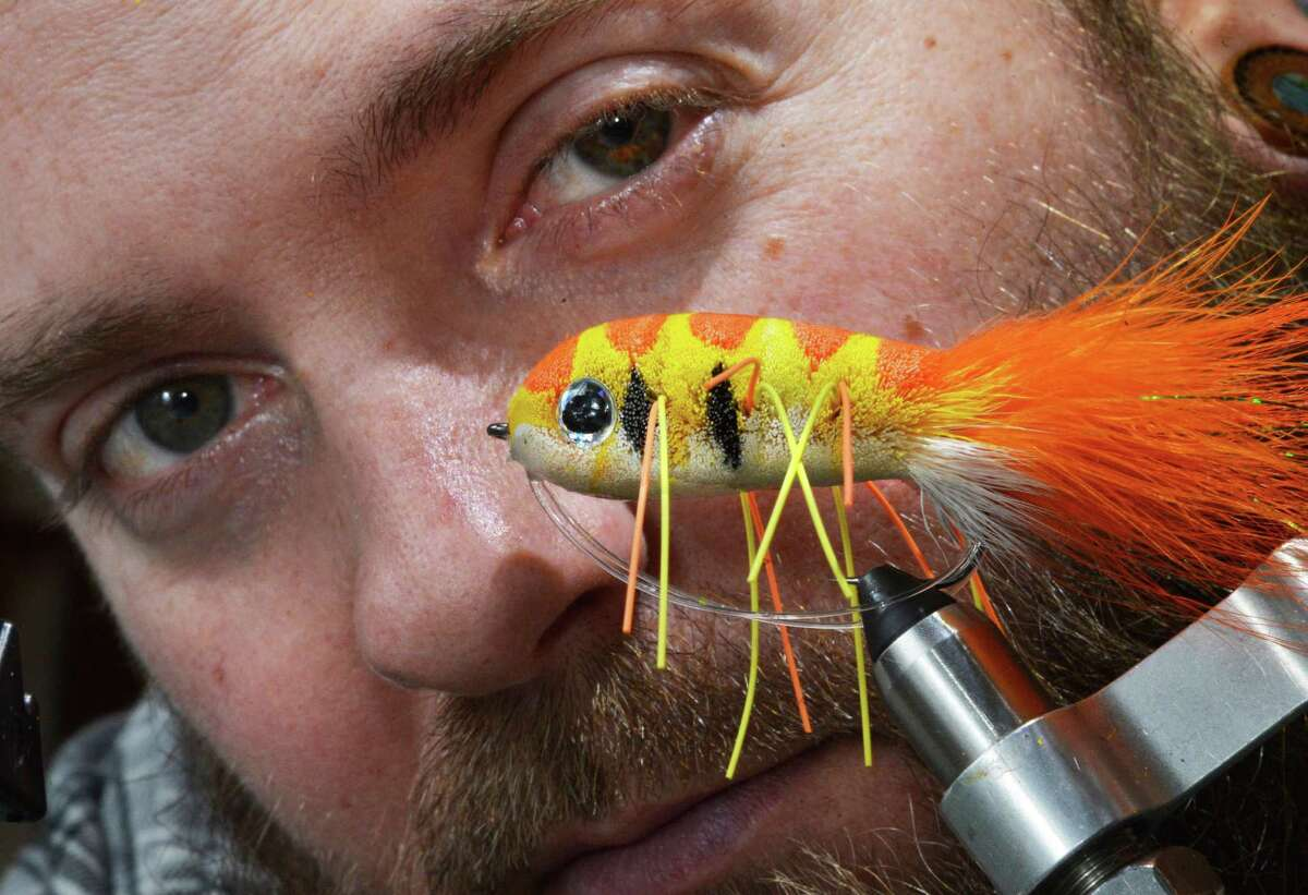 Fly tyer Pat Cohen with one of his Slip n' Slider, a large stacked deer hair fly in his Cobleskill studio Wednesday April 3, 2013. The Cobleskill native incorporated a youth spent chasing Schoharie Creek bass with skills honed as a tattoo artist to produce monster-sized fly-fishing lures. He's creating a new wave of flies using traditional materials to produce some surprisingly untraditional flies. (John Carl D'Annibale / Times Union)