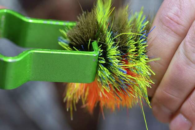 Fly tyer Pat Cohen uses his SF Fugly Packer to tighten stacked deer hair in constructing his Crank pattern at Cohen's Cobleskill studio Wednesday April 3, 2013.   (John Carl D'Annibale / Times Union) Photo: John Carl D'Annibale / 10021804A