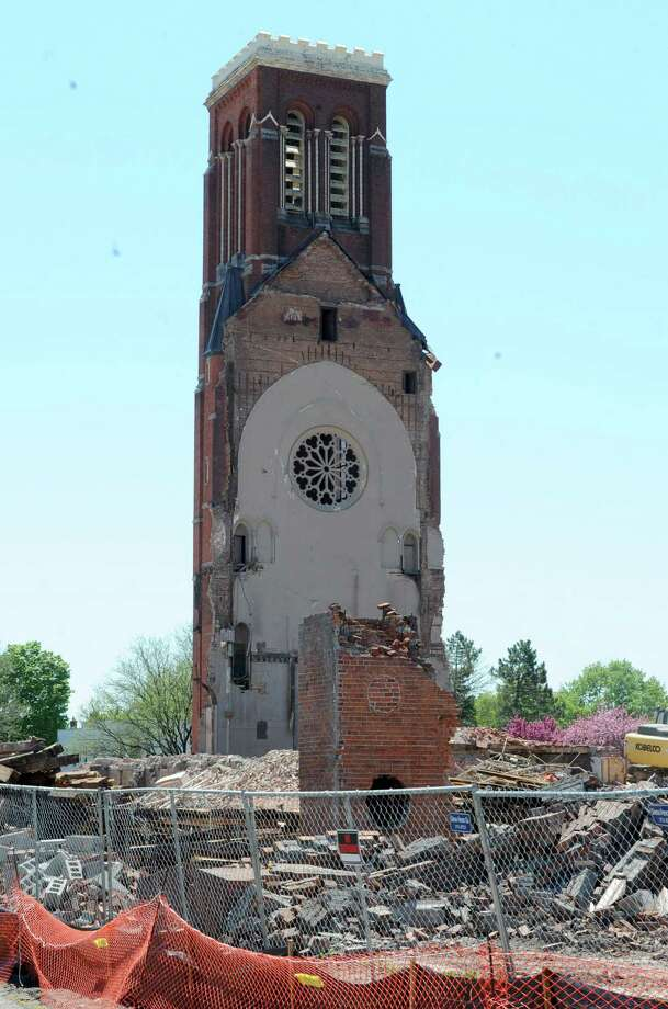 St. Patrick's Church's bell tower which is 137 feet tall still stands as debris from the demolition of the main part of the church is removed on Monday, May 6, 2013 in Watervilet, N.Y. By the end of the day or tomorrow they are supposed to cut off the top of the tower. (Lori Van Buren / Times Union) Photo: Lori Van Buren / 10022285B