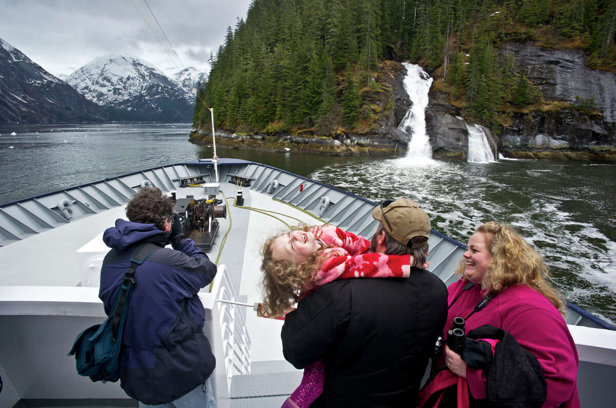 Kris Dorsey, right, her husband, Brian, and their daughter, Emma, 5, enjoys their time out on the deck of the Alaska State Highway ferry Malaspina during it's 50th Anniversary Golden Voyage cruise to Tracy Arm Fjord on Saturday, May 4, 2013, in Southeast Alaska. (AP Photo/The Juneau Empire, Michael Penn)