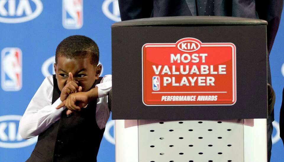 Miami Heat's LeBron James' son, Bryce, reacts as his father speaks during an NBA basketball news con