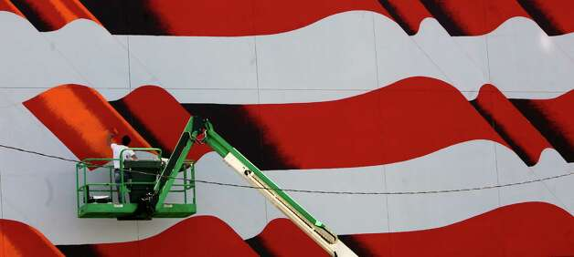Scott LoBaido works from a man lift painting a United States flag on the downtown Tampa Firefighters Museum on Monday, May 6, 2013, in Tampa, Fla.  (AP Photo/The Tampa Bay Times, Skip O'Rourke) Photo: Skip O'rourke, Associated Press / Tampa Bay Times
