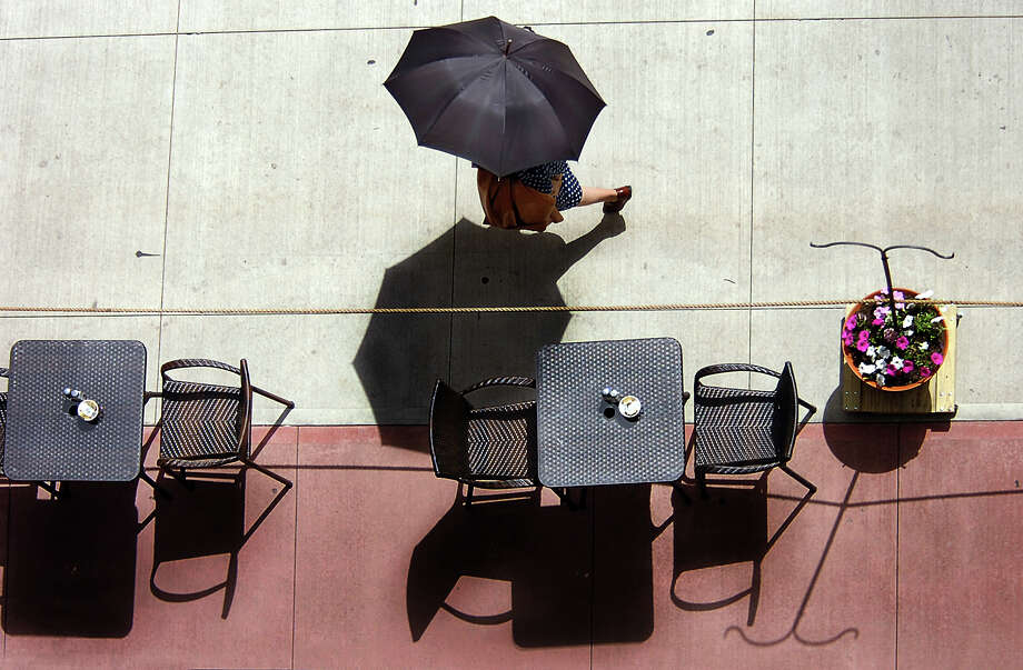 A pedestrian shades herself with an umbrella while walking along Linden Street on Monday, May 6, 2013 in downtown Scranton, Pa.  (AP Photo/The Scranton Times-Tribune, Butch Comegys) Photo: Butch Comegys, Associated Press / The Scranton Times & Tribune