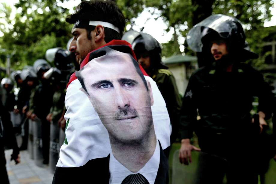 An Syrian man wrapped in a Syrian flag with a portrait of President Bashar Assad, walks past anti riot police during an anti-Israeli demonstration in front of the UN office in Tehran, Iran, Monday, May 6, 2013. Iran Condemns Israeli Air strikes on Syria and urged countries in the region to stand against the attack. (AP Photo/Ebrahim Noroozi) Photo: Ebrahim Noroozi, Associated Press / AP