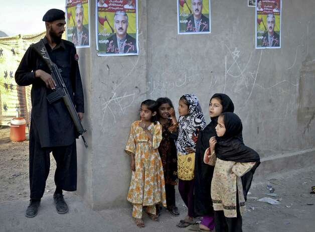 "In this Monday, May 6, 2013 photo, Pakistani children look at a soldier standing guard at an entrance of a  compound where an election rally is held in Quetta, Pakistan. The graffiti on walls around this Pakistani provincial capital hold a dire warning ahead of this weekend's national elections, ""Voting means death."" It's a very real threat: Over recent weeks at least six people have been killed and nearly 40 wounded in bombings and grenade attacks targeting candidates. (AP Photo/Arshad Butt) Photo: Arshad Butt, Associated Press / AP"