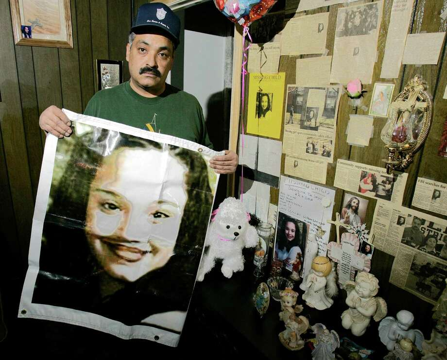 FILE - In this Friday, March 3, 2004 file photos shows Felix DeJesus, holding a banner showing his daughter's photograph, standing by a memorial in his living room in Cleveland. Cleveland police say two women who went missing as teenagers about a decade ago have been found alive in a residential area about two miles south of downtown. Cheering crowds gathered Monday night on the street near the home where police say Amanda Berry, Gina DeJesus and a third woman were found earlier in the day. The identity of the third woman hasn't been confirmed. (AP Photo/Tony Dejak, File) Photo: Tony Dejak
