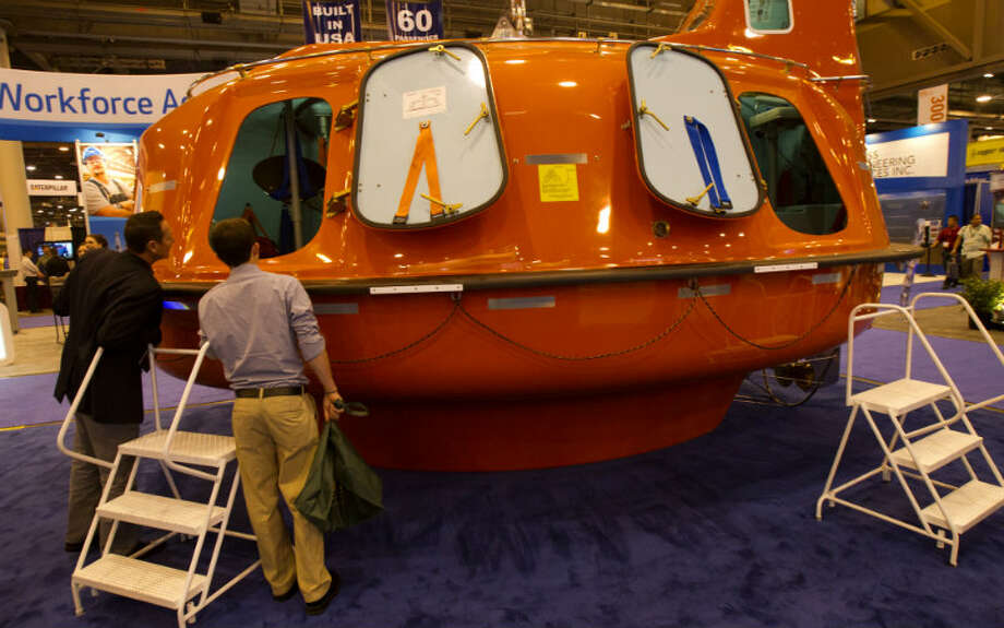 Rafael Ramos, left, and Chaston Collins, right, look at a life boat during the Offshore Technology Conference at Reliant Center Monday, May 6, 2013, in Houston. (Cody Duty / Houston Chronicle)