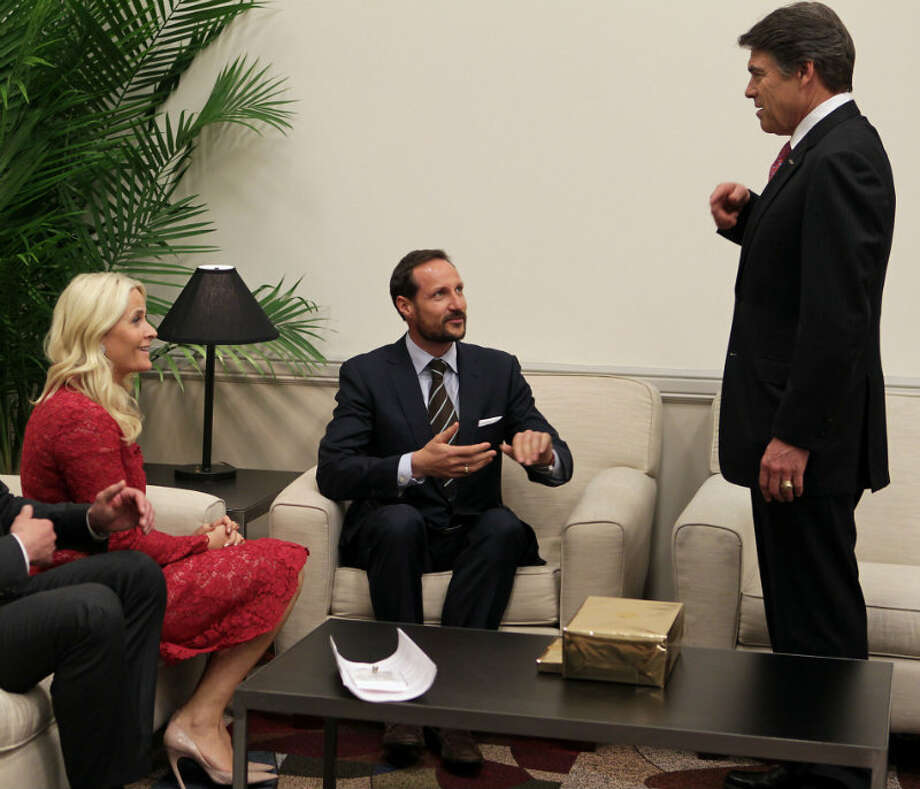 Norway's Crown Prince Haakon center, speaks Texas Governor Rick Perry right, as Crown Princess Mette-Marit left, looks on at OTC 2013 at Reliant Park Monday, May 6, 2013, in Houston. ( James Nielsen / Houston Chronicle