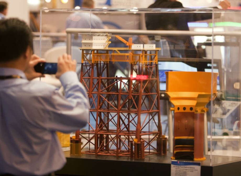 Kenny Chew takes a picture of a Fixed Platform Systems model during the Offshore Technology Conference at Reliant Center Monday, May 6, 2013, in Houston. (Cody Duty / Houston Chronicle)