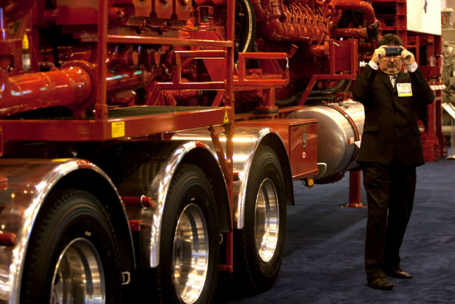 Tony Carey takes a picture as he stands in front of a Stewart & Stevenson Tier 4i Emissions-Compliant Fracturing Pumper during the Offshore Technology Conference at Reliant Center Monday, May 6, 2013, in Houston. (Cody Duty / Houston Chronicle)