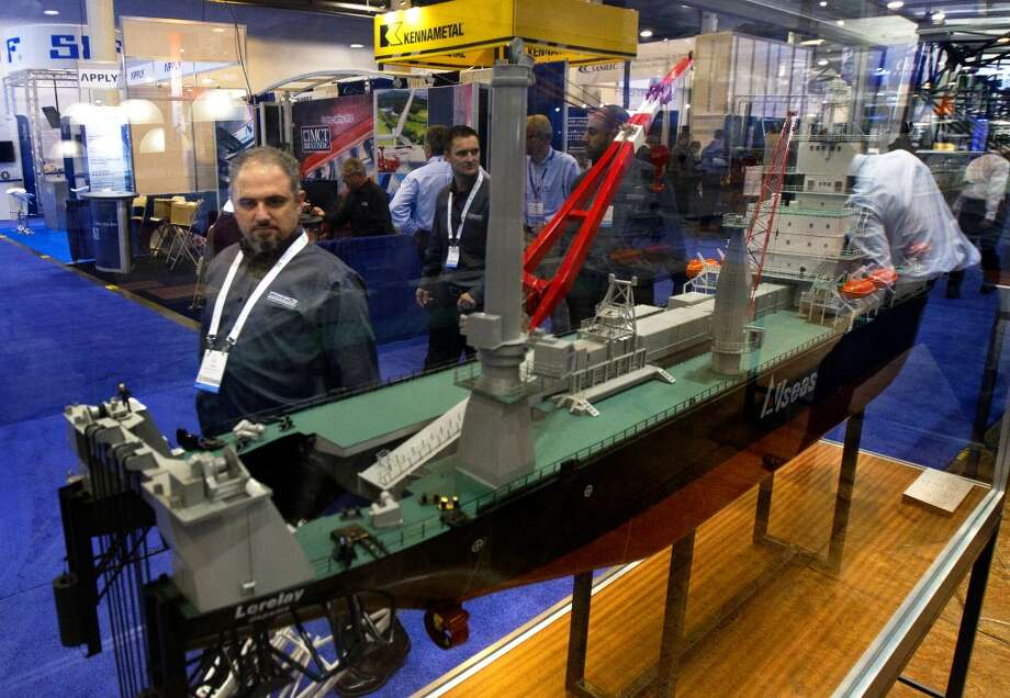 Ski Vernon, left, walks by a Lorelay DP Pipelay Vessel during the Offshore Technology Conference at Reliant Center Monday, May 6, 2013, in Houston. (Cody Duty / Houston Chronicle) Photo: Cody Duty, Houston Chronicle