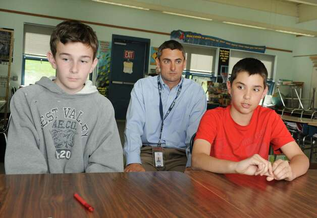 Sixth grader Calvin Fluegge, 11, right, talks about a new approach to teaching and learning at Boght Elementary School on Monday, May 6, 2013 in Colonie, N.Y. Sixth grader Ashton Britt, 12, and sixth grade teacher Pete Hanrahan sit next to him.  (Lori Van Buren / Times Union) Photo: Lori Van Buren / 10022284A