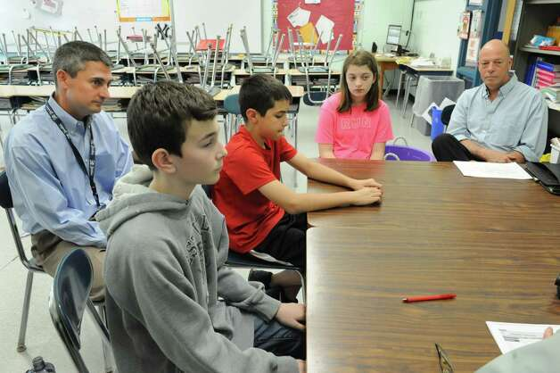 From left, sixth grade teacher Pete Hanrahan sits with his students Ashton Britt, 12, Calvin Fluegge, 11, and Lauren Halek, 11, as they talk about a new approach to teaching and learning at Boght Elementary School on Monday, May 6, 2013 in Colonie, N.Y. Instructional technology specialist Gary Cimorelli sits on right. (Lori Van Buren / Times Union) Photo: Lori Van Buren / 10022284A