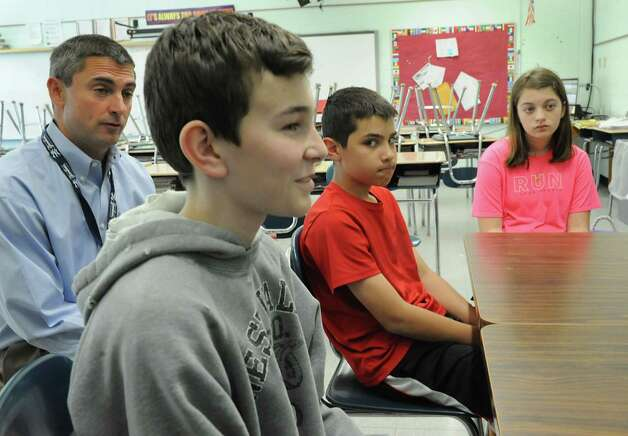 From left, sixth grade teacher Pete Hanrahan sits with his students Ashton Britt, 12, Calvin Fluegge, 11, and Lauren Halek, 11, as they talk about a new approach to teaching and learning at Boght Elementary School on Monday, May 6, 2013 in Colonie, N.Y. (Lori Van Buren / Times Union) Photo: Lori Van Buren / 10022284A