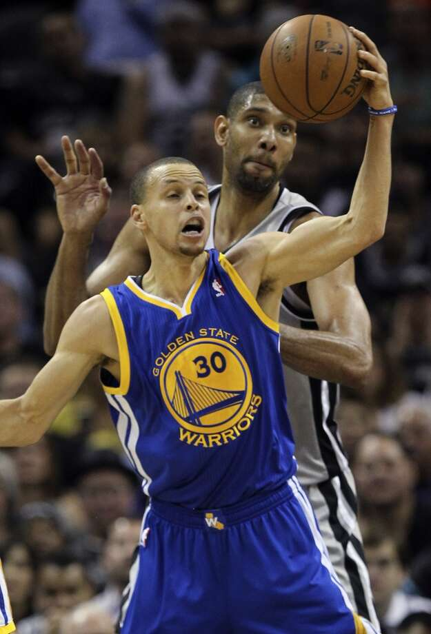 The Warriors' Stephen Curry gets control of the ball as the Spurs' Tim Duncan defends during the first half of Game 1 in the Western Conference semifinals at the AT&T Center, Monday, May 6, 2013.