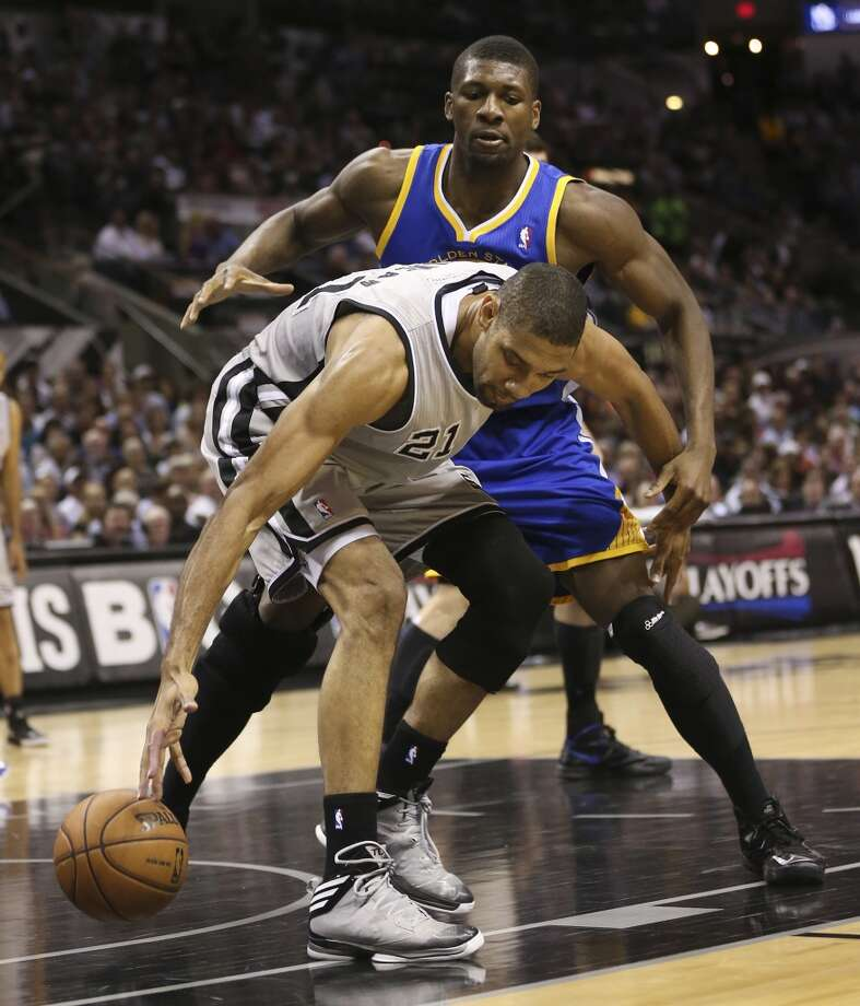 The Spurs' Tim Duncan tries to get control of the ball under pressure from the Warriors' Festus Ezeli during the first half of Game 1 in the  Western Conference semifinals at the AT&T Center, Monday, May 6, 2013.