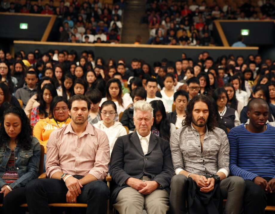 Barry Zito (second from left l to r), of the San Francisco Giants; director David Lynch; actor Russell Brand and Chris Lacayo, 16, junior at Phillip and Sala Burton Academic High School meditate with students during the 6th anniversary celebration of the San Francisco Unified School District Quiet Time program at Phillip and Sala Burton Academic High School in San Francisco, Calif., on Monday May 6, 2013.