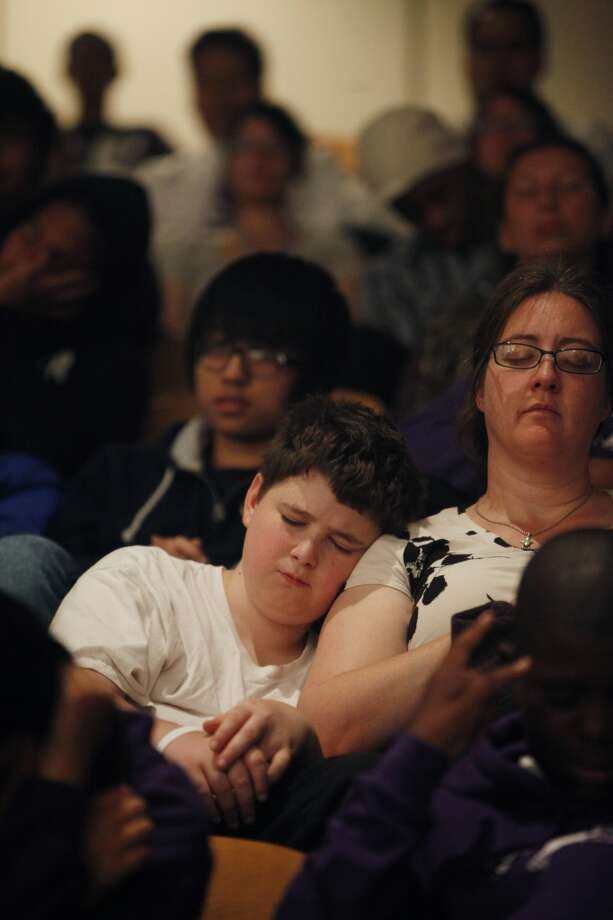 Isaac Lee (l to r), 13, of Visitacion Valley Middle School leans against his mother Heather Lee during group quiet time held during the 6th anniversary celebration of the San Francisco Unified School District Quiet Time program at Phillip and Sala Burton Academic High School in San Francisco, Calif., on Monday May 6, 2013.