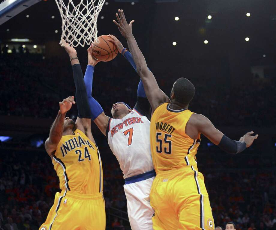 Knicks forward Carmelo Anthony (center) struggled while trying to split the defense of Indiana's Paul George (24) and center Roy Hibbert during Game 1. Photo: Barton Silverman / New York Times