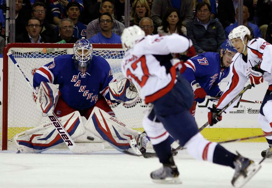 Washington Capitals defenseman Karl Alzner (27) takes a shot as New York Rangers goalie Henrik Lundqvist (30), of Sweden, defends the crease in the second period of Game 3 of their first-round NHL hockey Stanley Cup playoff series in New York, Monday, May 6, 2013. (AP Photo/Kathy Willens) Photo: Kathy Willens