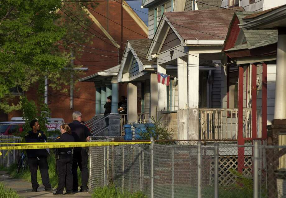 Cleveland police stand outside a home on just south of downtown where they say missing women Amanda Berry, Gina DeJesus and Michele Knight were found and where a man was arrested. Photo: Scott Shaw / Plain Dealer