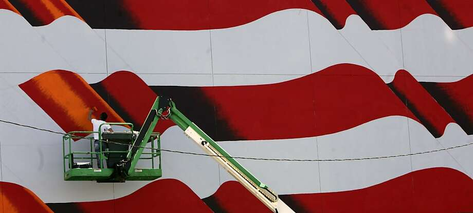 Scott LoBaido works from a man lift painting a United States flag on the downtown Tampa Firefighters Museum on Monday, May 6, 2013, in Tampa, Fla.  (AP Photo/The Tampa Bay Times, Skip O'Rourke) TAMPA OUT; CITRUS COUNTY OUT; PORT CHARLOTTE OUT; BROOKSVILLE HERNANDO OUT; USA TODAY OUT; MAGS OUT Photo: Skip O'rourke, Associated Press