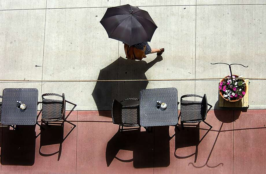 A pedestrian shades herself with an umbrella while walking along Linden Street on Monday, May 6, 2013 in downtown Scranton, Pa.  (AP Photo/The Scranton Times-Tribune, Butch Comegys) WILKES BARRE TIMES-LEADER OUT; MANDATORY CREDIT Photo: Butch Comegys, Associated Press