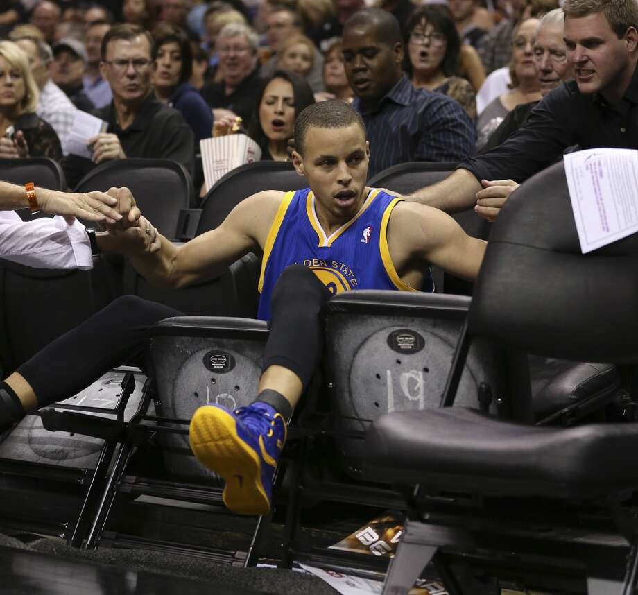 Golden State Warriors' Stephen Curry lands on seats during the second half of Game 1 in the NBA Western Conference semifinals against the San Antonio Spurs at the AT&T Center, Monday, May 6, 2013. The Spurs won in double overtime 129-127.