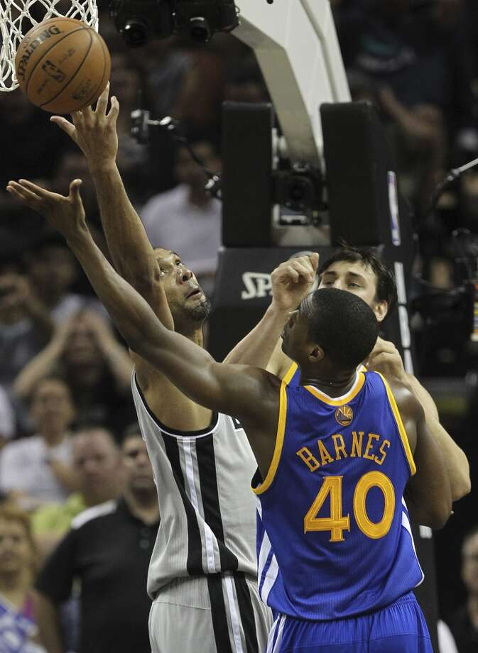San Antonio Spurs' Tim Duncan goes for a rebound against Golden State Warriors' Harrison Barnes during the second half of Game 1 in the NBA Western Conference semifinals at the AT&T Center, Monday, May 6, 2013. The Spurs won in double overtime 129-127.