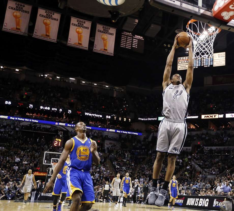 San Antonio Spurs' Kawhi Leonard goes up for a dunk around Golden State Warriors' Harrison Barnes in Game 1 of the NBA Western Conference semifinals Monday May 6, 2013 at the AT&T Center. The Spurs won 129-127 in double overtime.