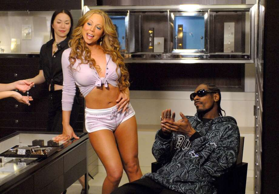 Mariah Carey and Snoop Dogg film a scene for a music video at a Louis Vuitton store in Los Angeles.