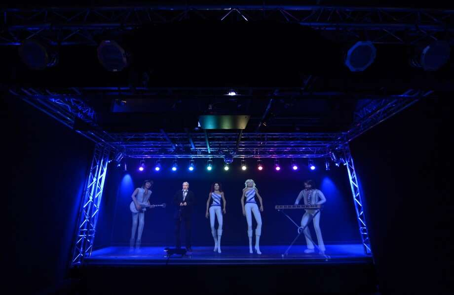 A man singing karaoke with a hologram featuring ABBA members at the world's first permanent ABBA museum.