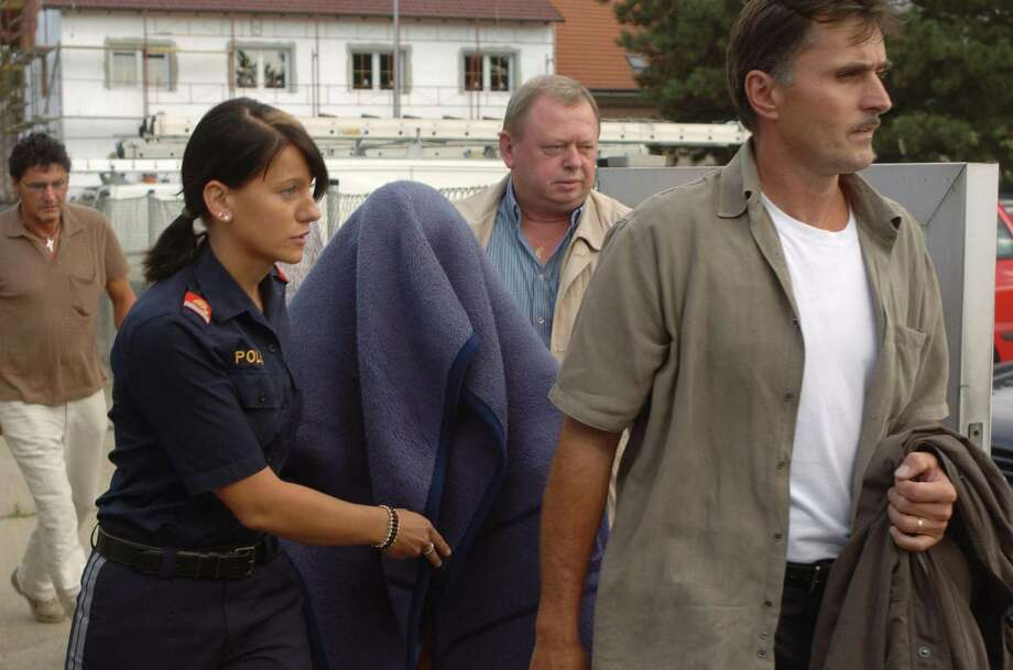 Kampusch is shown being escorted by police from the house where she was held for eight years in Strasshof, Austria in 2006. Photo: STR, Getty / 2006 AFP