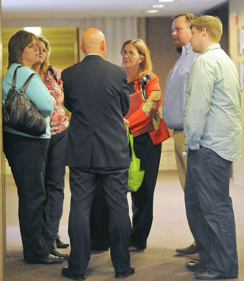 Assistant District Attorney Perry Thomas, back to camera, and Cathy Bell-Schexnaider with MADD in orange, talk with Todd Holtzclaw, second from right, and others, in a hallway after leaving Judge Walker's courtroom. A manslaughter trial that was supposed to start Monday afternoon May 6, 2013 for a traffic accident that killed a woman and her nine month old toddler in January of 201, was postponed again.  Alyssa Holtzclaw was driving her nine month-old son to the family's home in Sour Lake on highway 105 when a suspected drunk driver t-boned their car, killing both. The suspect, Inez Legarda, didn't have a license and fled the scene. He's charged w/ two counts of manslaughter. Dave Ryan/The Enterprise Photo: Dave Ryan