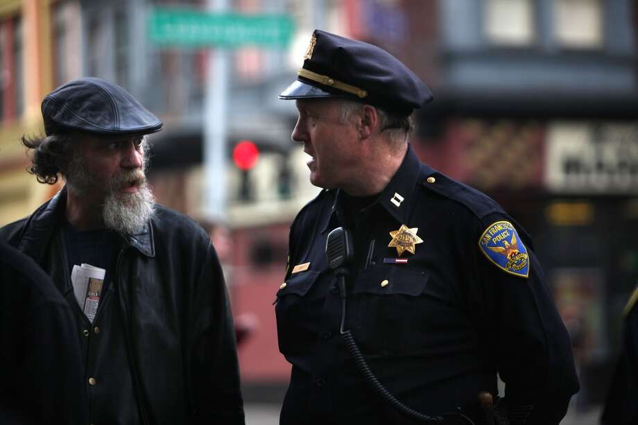 Tenderloin captain Joe Garrity talks with a neighborhood resident as city attorney Dennis Herrera announced a filing today of civil lawsuits against two Tenderloin businesses in San Francisco, Calif., on Monday, January 30, 2012.