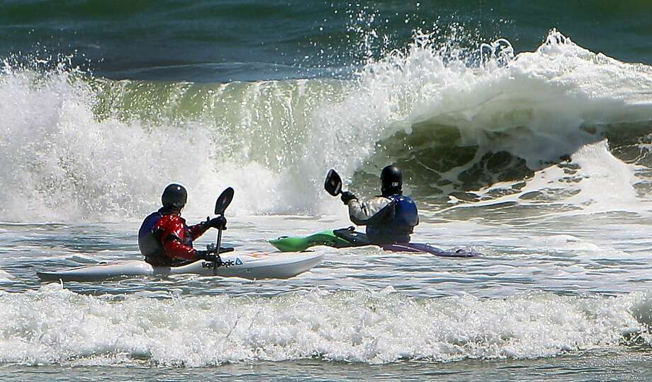 Catching a wave - in their lap: Kayakers brave the Atlantic in Rye, N.H. Photo: Jim Cole, Associated Press