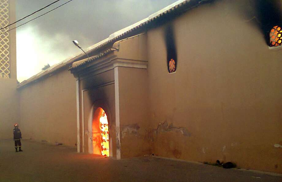 Too hot to enter: A firefighter watches flames dance in the entrance to the great mosque of Taroudant in southern Morocco. The mosque was heavily damaged by the fire, which authorities say started accidentally. Photo: Str, AFP/Getty Images