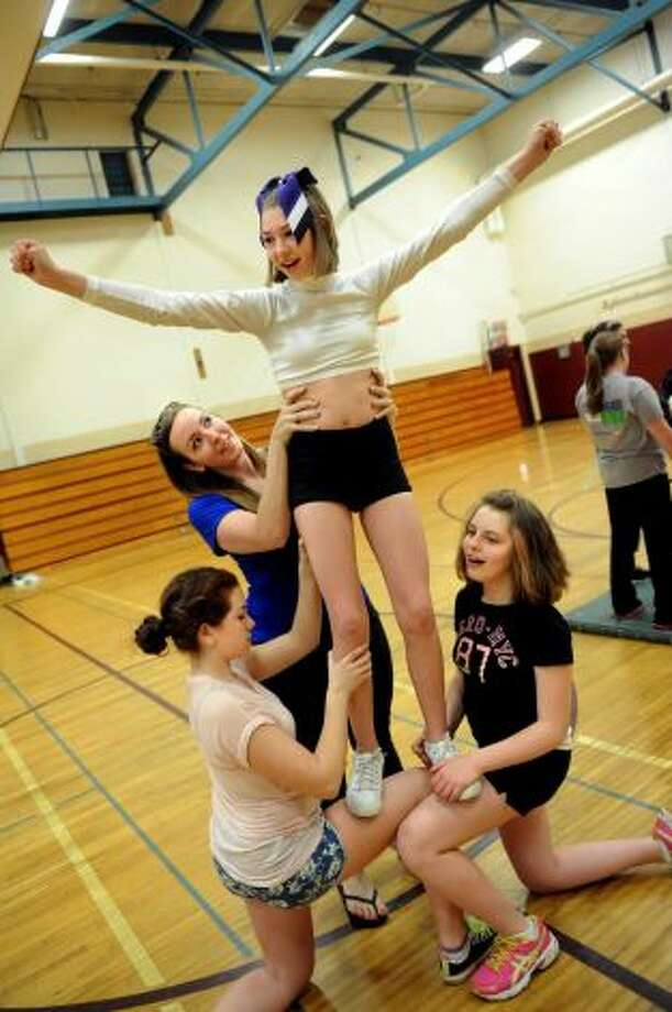 Emily Maye, 14, center, flies high as she practices a cheer routine with The Angels on Thursday, May 2, 2013, at Sand Creek Middle School in Colonie, N.Y. Supporting her are helpers Jackie Rinaldi, left, Rachael Blaine, second from left, and cheer member Hailey Murphy, 12. The Capital District Challenger Cheer team will perform for the President's Council on Physical Fitness in Washington D.C. (Cindy Schultz / Times Union)