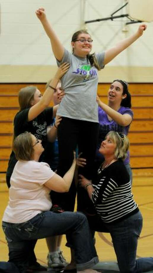 This image reminds me of that iconic Iwo Jima picture.  Julia Huber, 15, of Bethlehem does a lift with some support from volunteers during practice  with The Angels on Thursday, May 2, 2013, at Sand Creek Middle School in Colonie, N.Y. The Capital District Challenger Cheer team will perform for the President's Council on Physical Fitness in Washington D.C. (Cindy Schultz / Times Union)