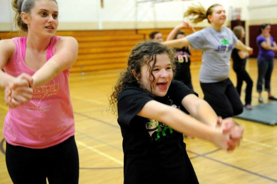 Francesca Citone, 13, center, and her helper Katie Hutton, 16, left, practice a cheer routine with The Angels on Thursday, May 2, 2013, at Sand Creek Middle School in Colonie, N.Y. The Capital District Challenger Cheer team will perform for the President's Council on Physical Fitness in Washington D.C. (Cindy Schultz / Times Union)