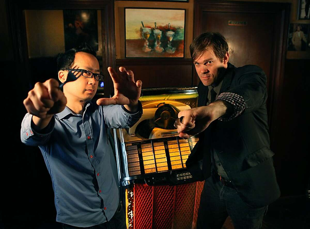 Prince Gomolvilas (left) and Brandon Patton (right) pose in front of the vintage jukebox at Tosca in San Francisco, Calif., on Monday, May 6, 2013. They star in a new show at Berkeley's Impact Theatre called