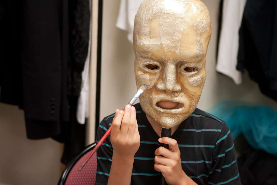 "A mask hides Paris Bezanis, 15, who is accustomed to working in the background designing theater sets for school productions. He designed a pagoda for a hypothetical production of  J.R.R. Tolkein's ""The Hobbit."" Photo: R. Clayton McKee, Freelance / © R. Clayton McKee"