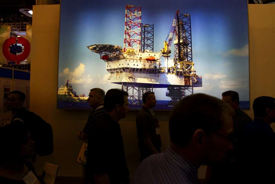 Attendees walks by an image of an offshore oil rig during day two of the Offshore Technology Conference at Reliant Center Tuesday, May 7, 2013, in Houston. (Cody Duty / Houston Chronicle) Photo: Cody Duty, Houston Chronicle