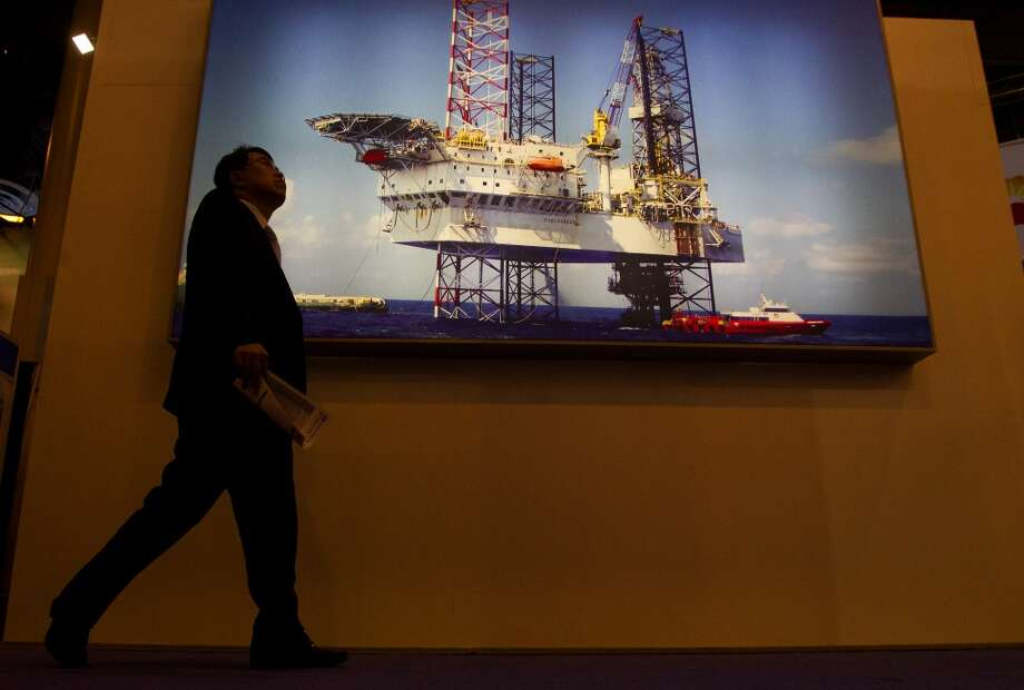 An attendee walks by an image of an offshore oil rig during day two of the Offshore Technology Conference at Reliant Center Tuesday, May 7, 2013, in Houston. (Cody Duty / Houston Chronicle) Photo: Cody Duty, Houston Chronicle